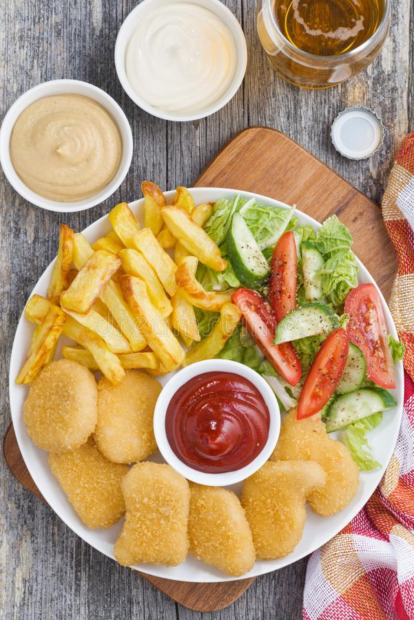 Lunch with chicken nuggets, french fries, fresh salad and beer. Top view, vertical stock photography