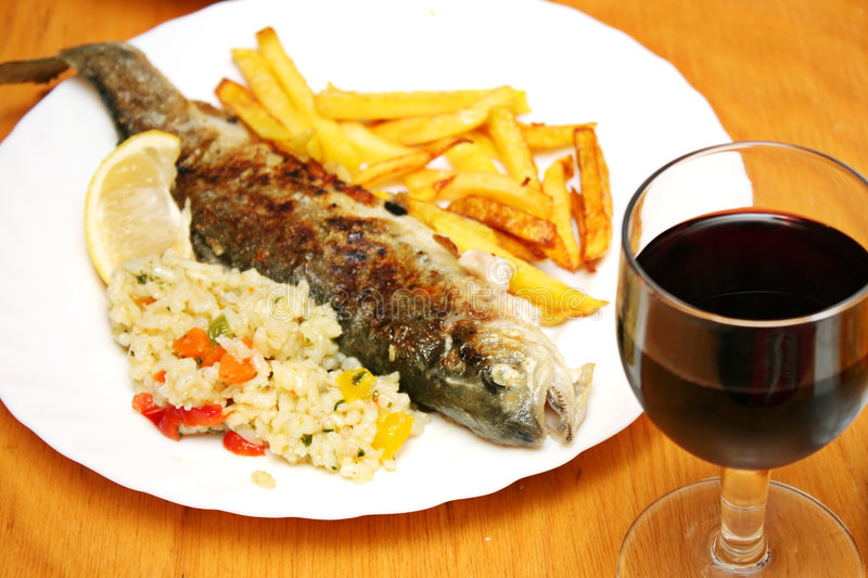 Lunch delicious trout fish. Food and red wine stock photography