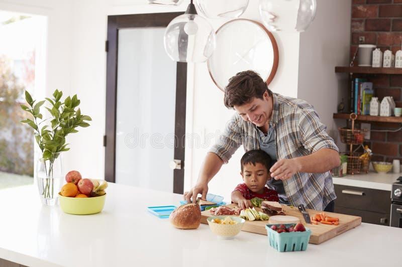 Lunch för faderAnd Son Making skola i kök hemma royaltyfri foto