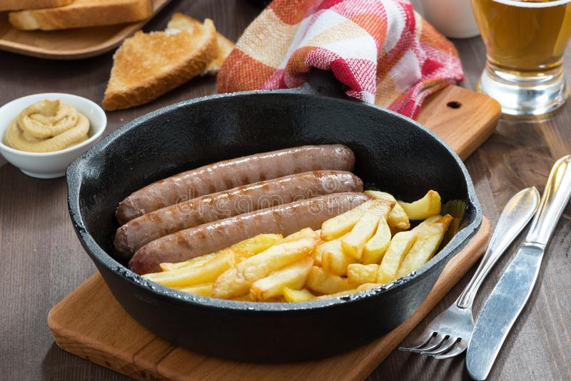 Lunch with grilled sausages, French fries, toast and beer. Close-up stock photo