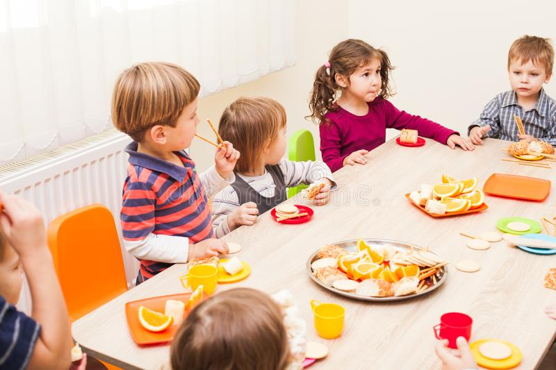 Lunch in kindergarden. Children are sitting at the table with lunch and eating fruits and cakes stock photos
