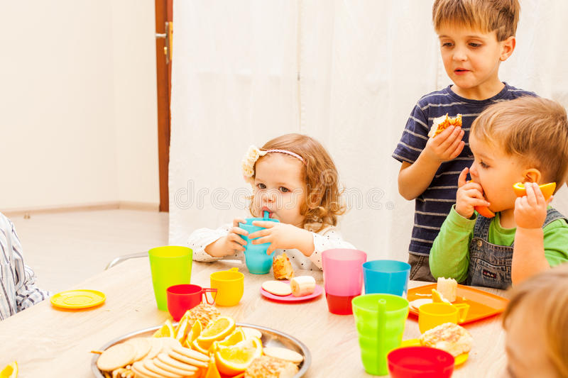 Lunch in kindergarden. Children are sitting at the table with lunch and eating fruits and cakes stock images