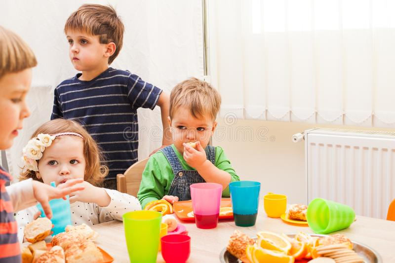 Lunch in kindergarden. Children are sitting at the table with lunch and eating fruits and cakes royalty free stock images