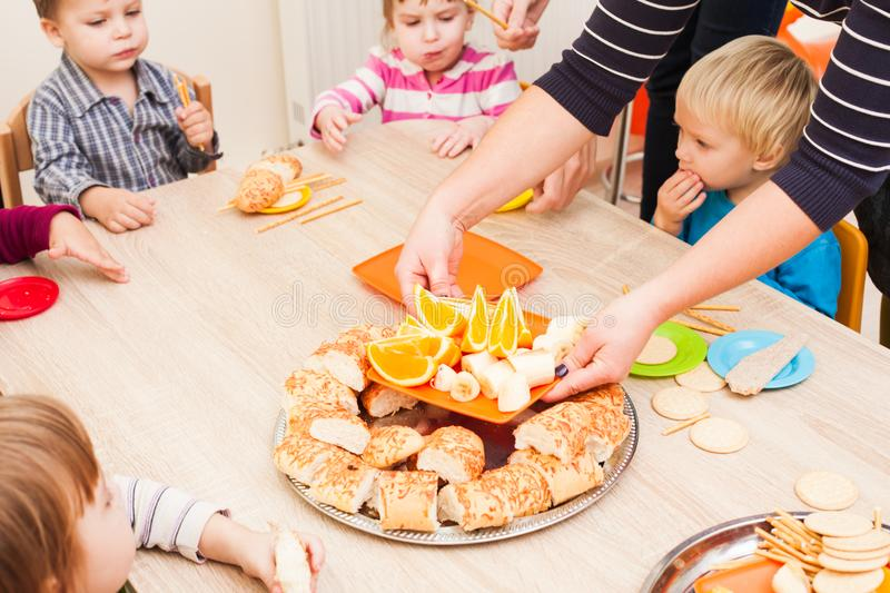 Lunch in kindergarden. Children are sitting at the table with lunch and eating ts and cakes royalty free stock photo