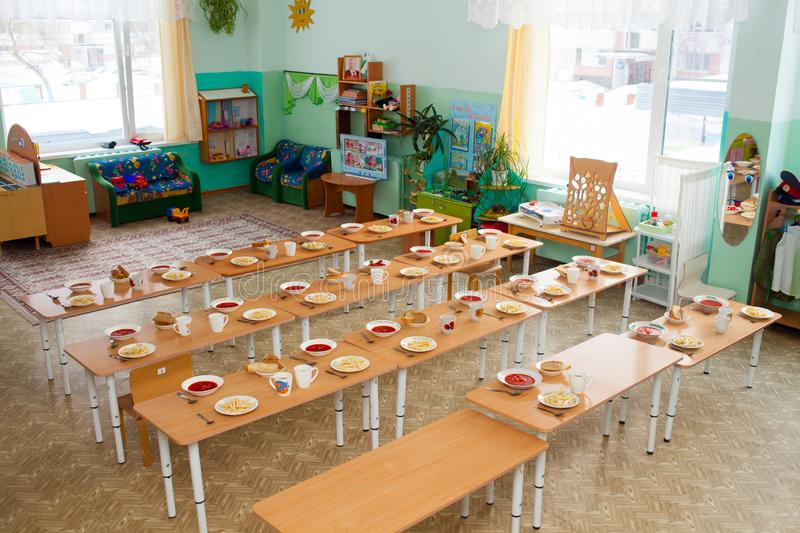 Lunch in kindergarten in Russia. Covered tables for children. Catering in kindergartens royalty free stock photo