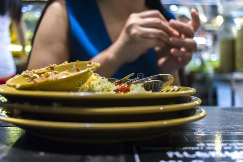 Lunch på en thailändsk restaurang En kvinna äter ris med grönsaker och soppa arkivbild