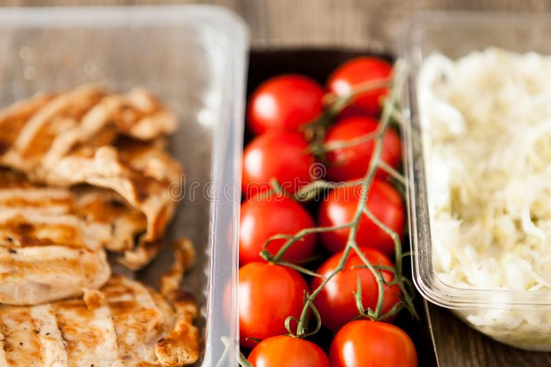 Lunch packed in different boxes. Fresh and healthy eating on wooden background royalty free stock photo