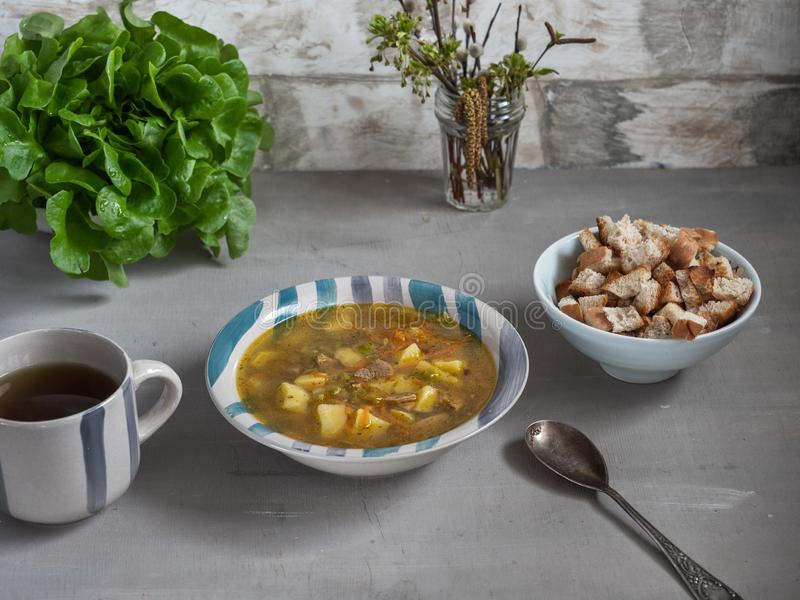 Lunch of pea soup with crackers, a bush of green lettuce in the background stock images