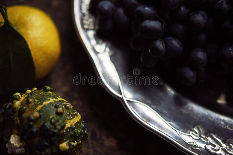 Lunch Provencal style still life on wooden table, flower pattern, seasonal vegetables, wine grapes, pumpkin, daylight. Lunch Provencal style still life on stock photos