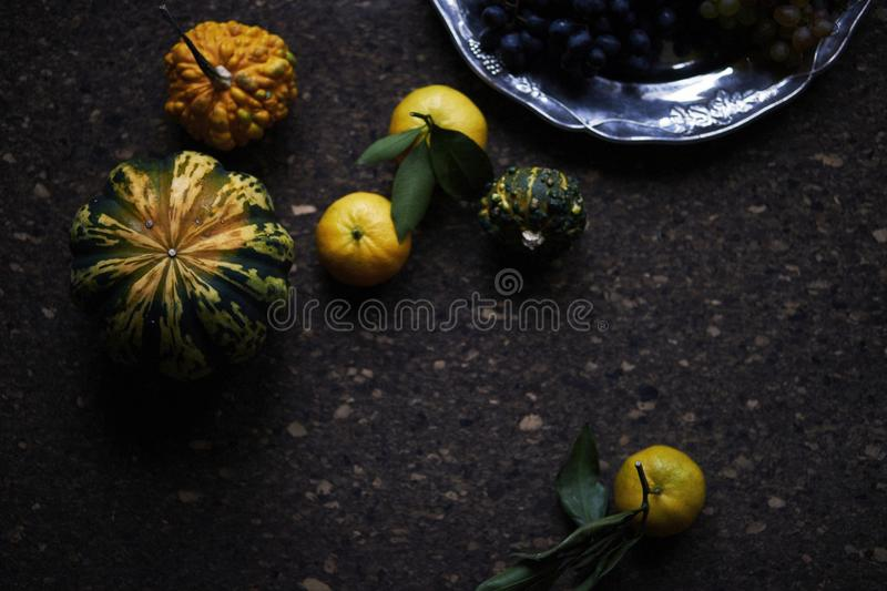 Lunch Provencal style still life on wooden table, flower pattern, seasonal vegetables, wine grapes, pumpkin, daylight. Lunch Provencal style still life on stock photography
