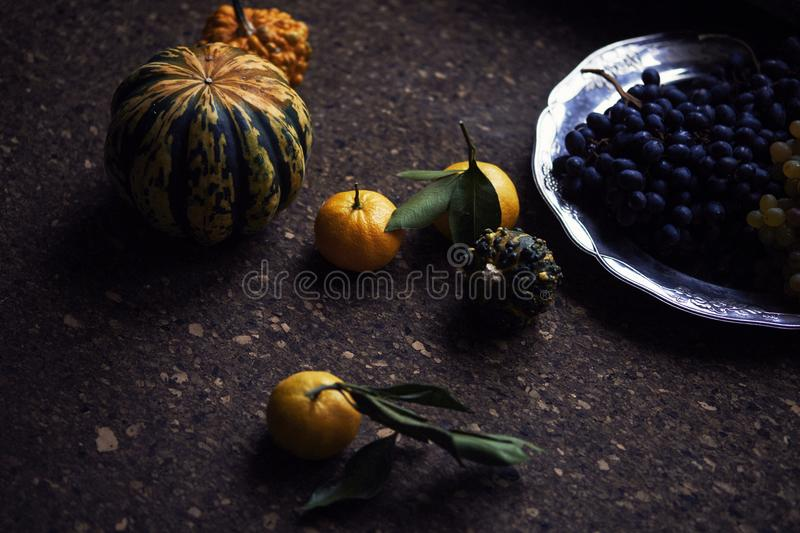 Lunch Provencal style still life on wooden table, flower pattern, seasonal vegetables, wine grapes, pumpkin, daylight. Lunch Provencal style still life on stock photo