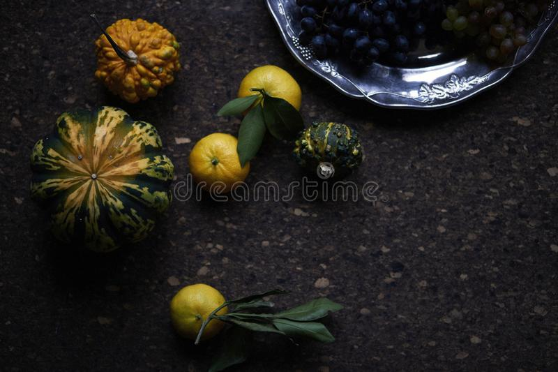 Lunch Provencal style still life on wooden table, flower pattern, seasonal vegetables, wine grapes, pumpkin, daylight. Lunch Provencal style still life on stock images