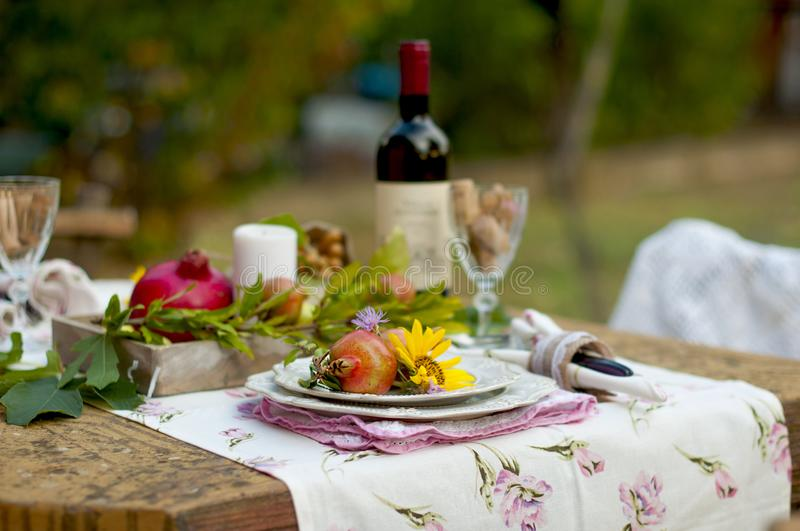 Lunch is romantic in autumn garden, atmosphere of holiday and coziness. Autumnal dinner in the open air with wine and fruit. Decor royalty free stock image
