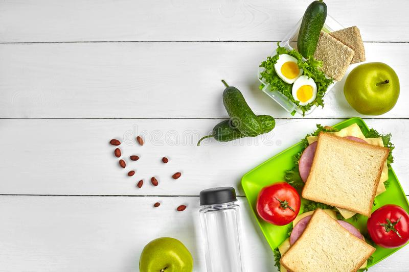 Lunch. Sandwich and fresh vegetables, bottle of water, nuts and fruits on white wooden background. Healthy eating royalty free stock photography