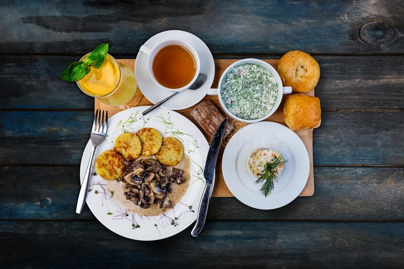 Lunch set. Okroshka, mushroom with hashbrowns and traditional russian salad, served on the tray with the cutlery. royalty free stock photography