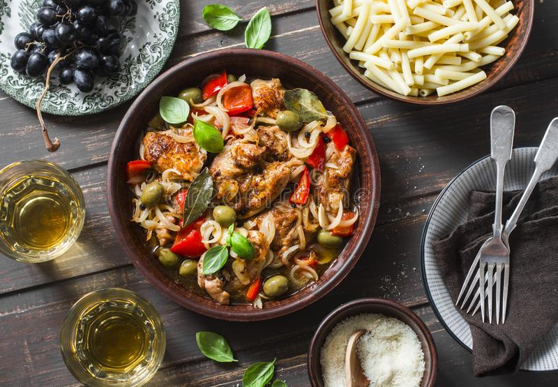Lunch table. Roasted chicken with olives and sweet peppers, paste, white wine on dark background, top view. royalty free stock photo