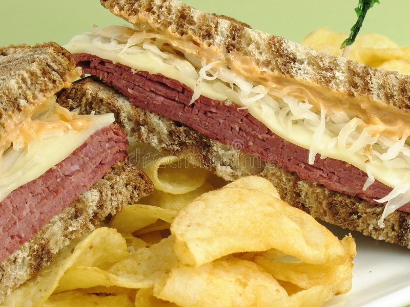 Lunch Time. Reuben sandwich with corned beef, melted swiss cheese, sauerkraut, and thousand island dressing on marble rye bread. Served with potato chips stock images