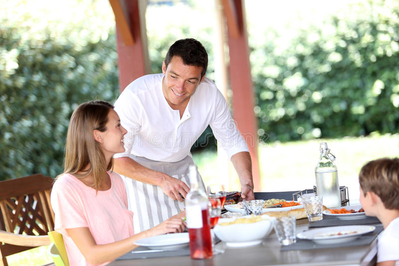 Lunch time at home. Man serving grilled food to family stock photography