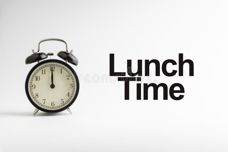 LUNCH TIME inscription written and alarm clock on white background royalty free stock photography