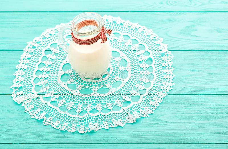 Lunch time with jug of milk and plaid ribbon on blue wooden background. Lace tablecloth. Selective focus royalty free stock images