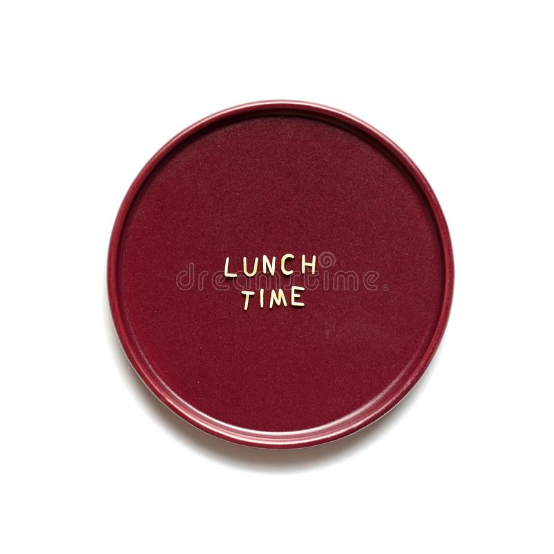 Lunch time made from macaroni letters on burgundy plate. Close up, isolated on white background stock photography