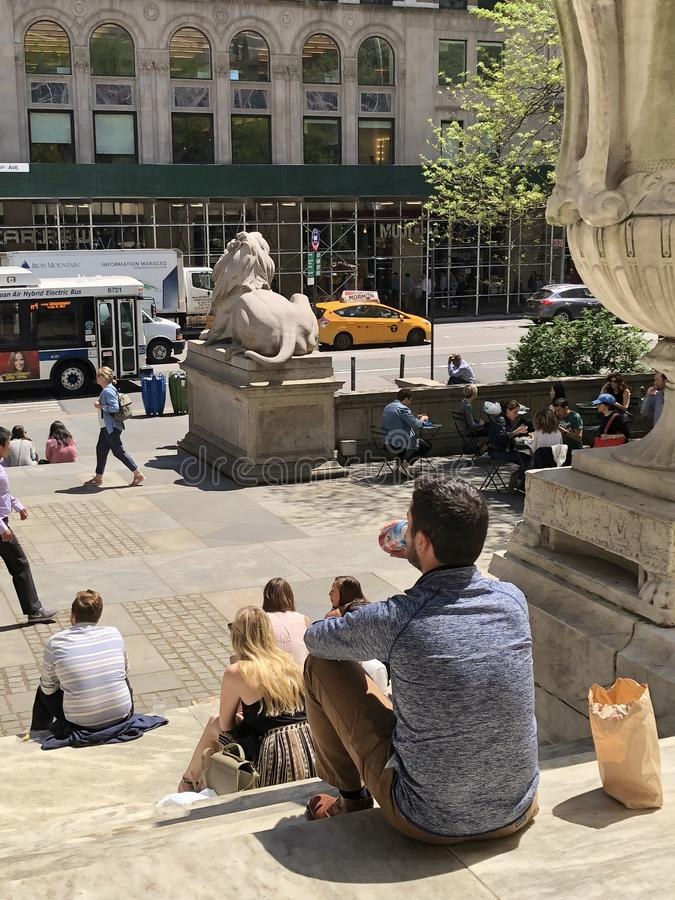 Lunch Time in Midtown New York City. People taking a break and sitting on steps of Morgan library on Fifth Avenue New York City royalty free stock photos