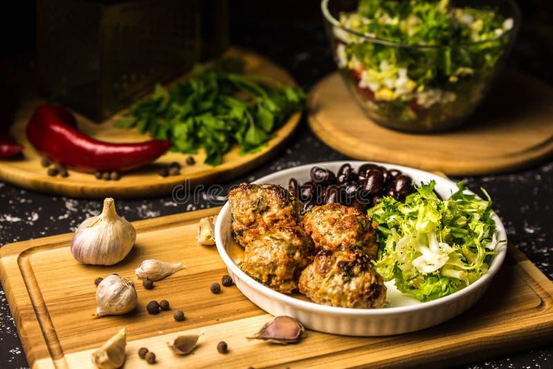 Lunch van vleesballetjes in tomatensaus, sla en zwarte bonen stock afbeeldingen