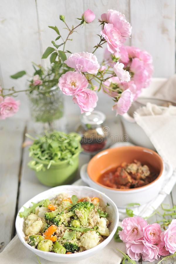 A lunch of vegetable salad, on a table with a bouquet of garden roses. Food for vegetarians. Wessen Lunch. A lunch of vegetable salad, on a table with a bouquet stock photos