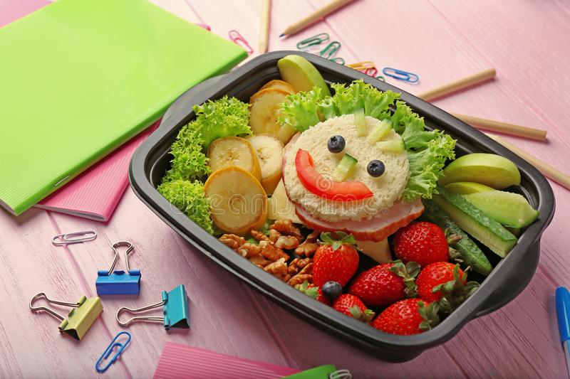 Lunchbox with dinner and stationery. On pink wooden background royalty free stock photo