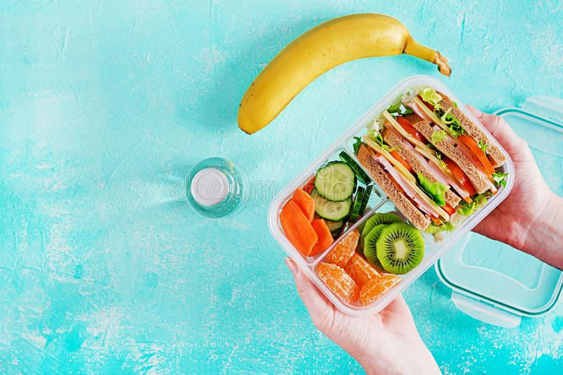 Lunchbox in hands. School lunch box with sandwich, vegetables, water, and fruits on table. Healthy eating habits concept. Flat lay royalty free stock photos