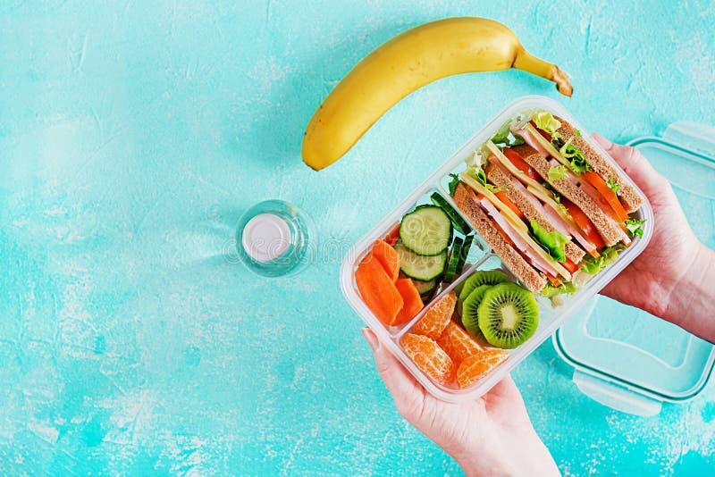 Lunchbox i händer Skolalunchask med smörgåsen, grönsaker, vatten och frukter på tabellen Sunt matvanabegrepp Lekmanna- lägenhet royaltyfria foton