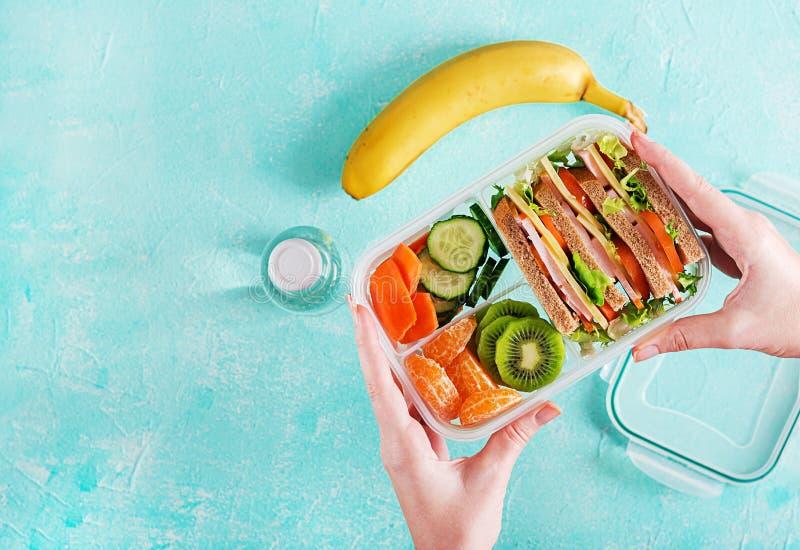 Lunchbox i händer Skolalunchask med smörgåsen, grönsaker, vatten och frukter på tabellen Sunt matvanabegrepp Lekmanna- lägenhet royaltyfri fotografi
