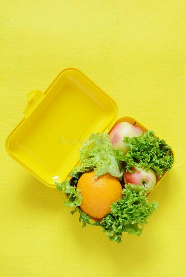 Lunchbox med mat Mogen orange fruktsaft, äpplen och grönsallat spricker ut på en gul bakgrund Bästa sikt, lekmanna- lägenhet, tak arkivfoton