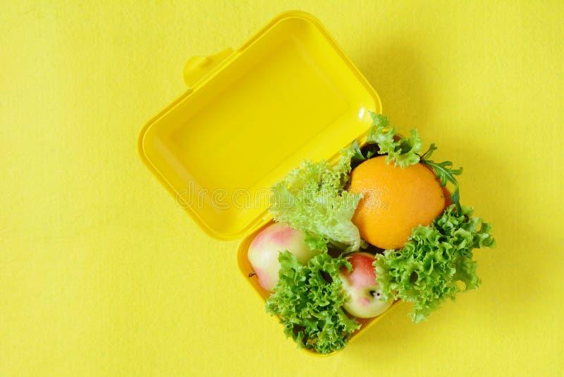 Lunchbox med mat Mogen orange fruktsaft, äpplen och grönsallat spricker ut på en gul bakgrund Bästa sikt, lekmanna- lägenhet, tak royaltyfria foton