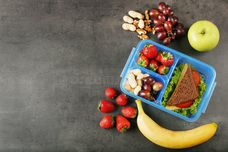 Lunchbox z kanapką i różnymi produktami na ciemnym tle zdjęcie stock