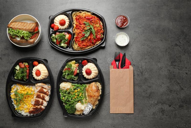 Lunchboxen mit verschiedenen Mahlzeiten auf dem grauen Tisch, flach gelegt lizenzfreies stockfoto