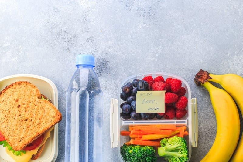 Lunchboxes con i panini e prodotti differenti su fondo grigio immagini stock