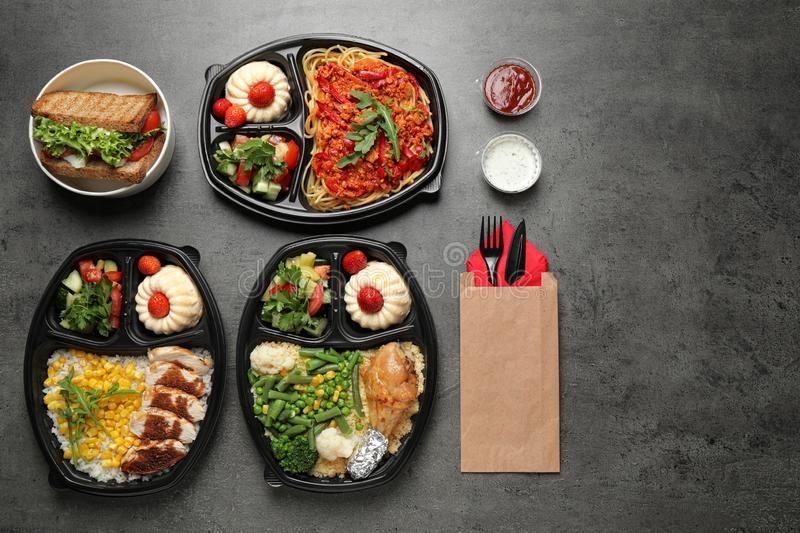 Lunchboxes with different meals on grey table, flat lay. Healthy food delivery royalty free stock photo