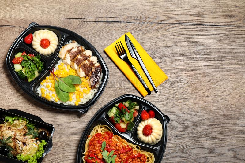 Lunchboxes with different meals on wooden table. Healthy food delivery. Lunchboxes with different meals on wooden table, flat lay. Healthy food delivery stock image