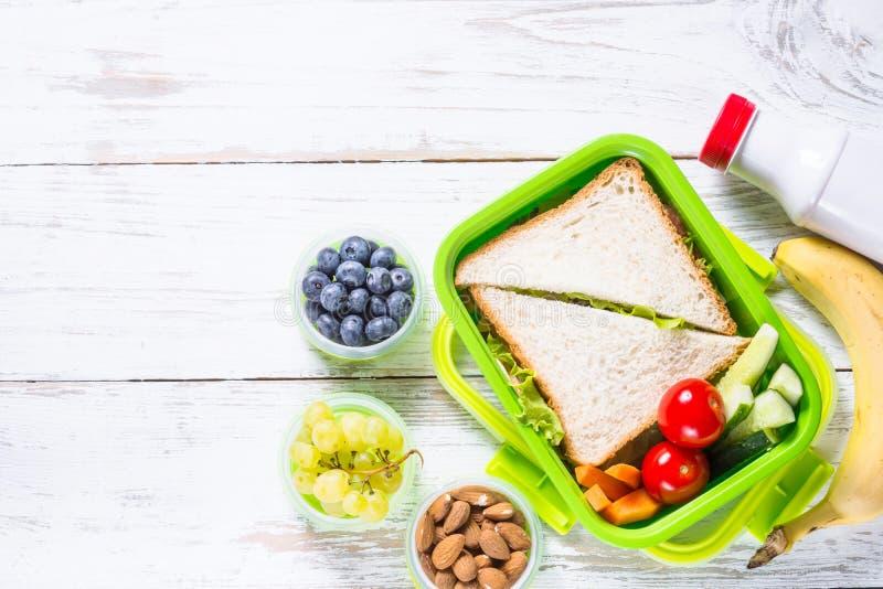 Lunchdoos met sandwich, groenten, yoghurt, noten en bessen royalty-vrije stock afbeelding