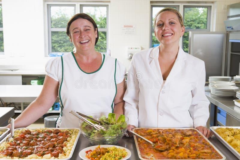Lunchladies neben Tellersegmenten der Nahrung in einer Schule stockbilder