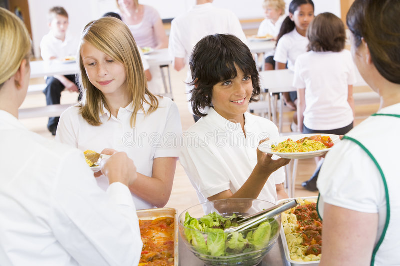 Lunchladies serving plates of lunch in a school royalty free stock image