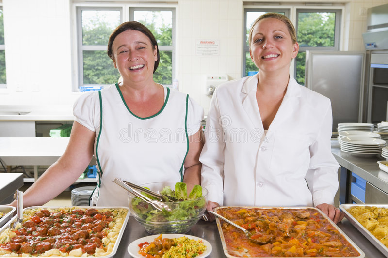 Lunchladies beside trays of food in a school. Lunchladies beside trays of food in school cafeteria stock images