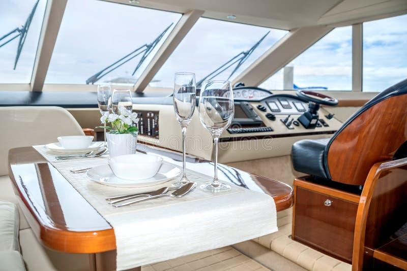 Lunchtabellinställning på en bekväm yachtinre royaltyfri fotografi