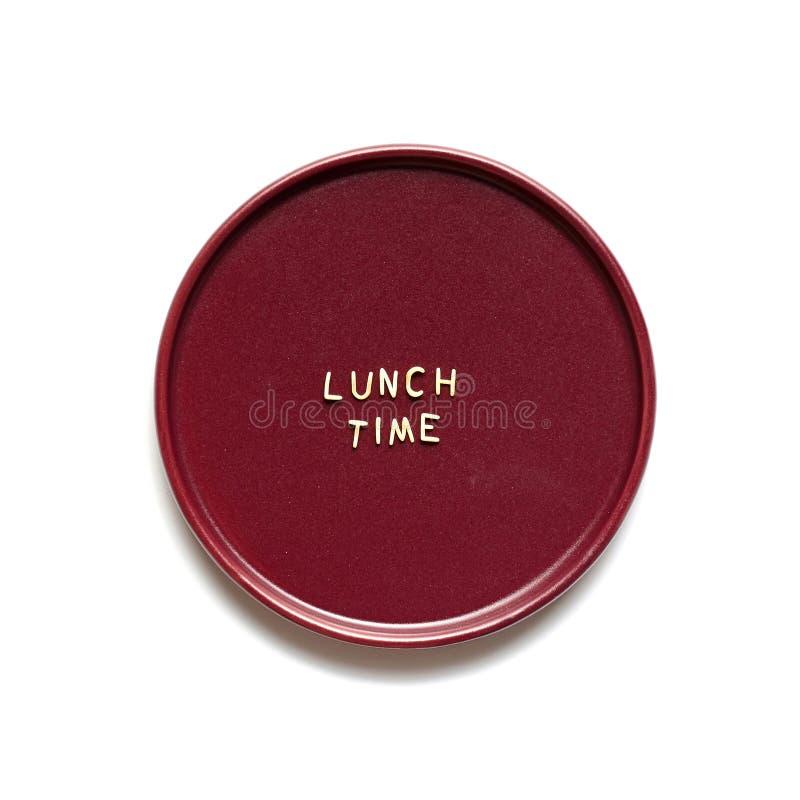 Lunchtid gjorde från makaronibokstäver på den burgundy plattan slut upp, isolerat p? vit bakgrund arkivbild