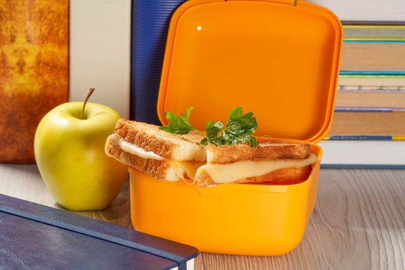 Lunchu pudełko z wznoszącymi toast plasterkami chleb, ser, zieleni pietruszka, zielony jabłko i hardback, rezerwuje na tle obraz stock