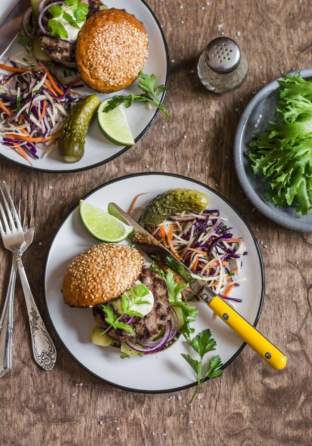 Lunchu stół dwa wołowiny domowej roboty hamburger i kapuściana sałatka na drewnianym stole -, odgórny widok zdjęcia royalty free