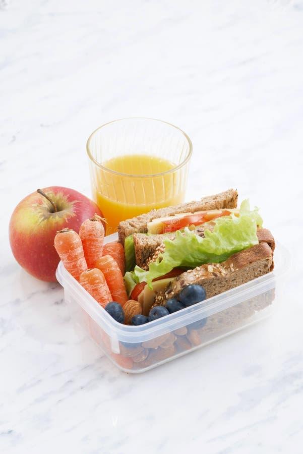 Lunchvakje met sandwich van volkorenbrood op lijst stock foto