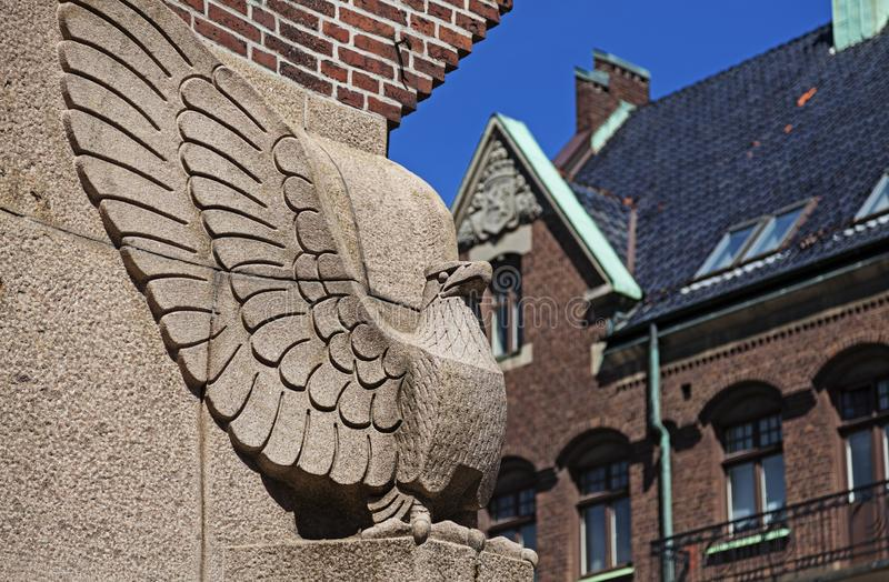 Stone eagle sitting in a street corner on building royalty free stock photos