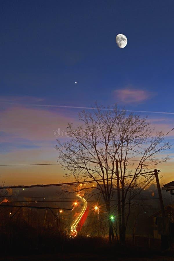 Lune au-dessus de ville orange photos stock